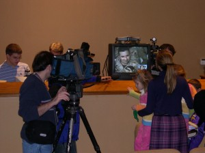 Twin Cities TV News Crews record every word of the first of many Eagan Hills Church services shared with deployed Marines in Fallujah, Iraq. Dec. 4, 2004.